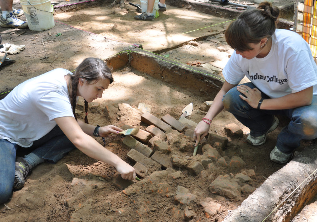 students excavating old chimney